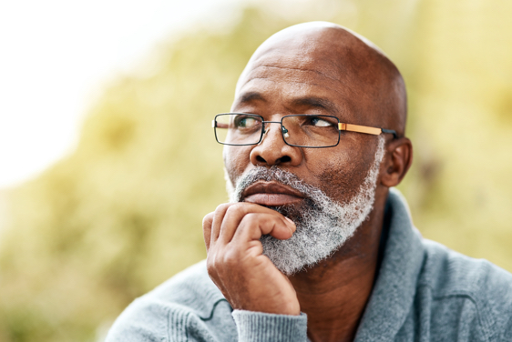 A man holding his hand to his chin in a thinking posture